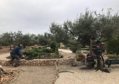 Reg per jardí i construcció de mur de pedra seca per jardinera